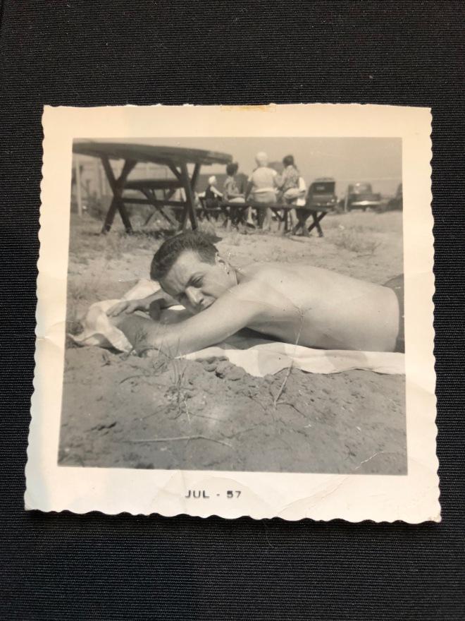 Dad lying on a sandy beach